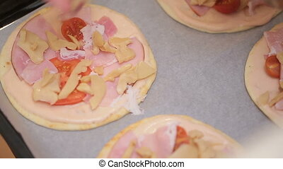 Female hand adding ingredients to home made pizza.