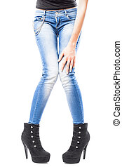 female hand and legs in jeans and high heels