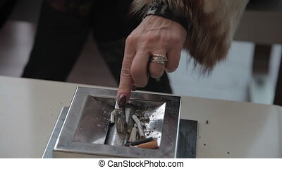 Female hand. Ashtray - Woman puts out the cigarette and...