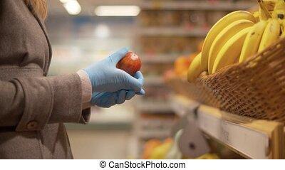 Female hand choosing oranges in the supermarket
