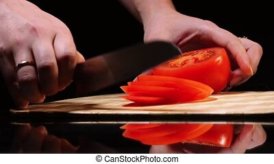Female hand close-up takes the knife and slices of ripe tomato on a cutting Board on a black background.