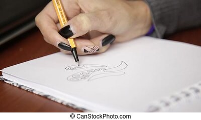 Female hand drawing a abstract flower with pencil in...