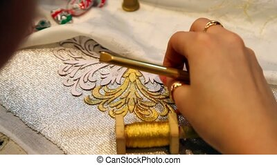 female hand embroider with gold thread and lace needle on...
