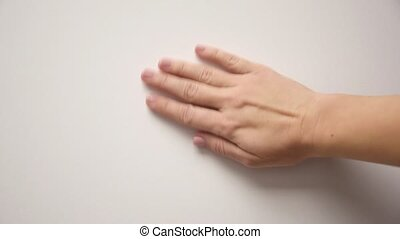 Female hand erases something from the wall