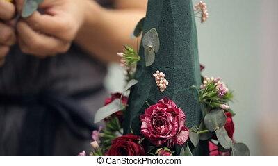 Female hand fills a bouquet florist floral decorations on the foam.