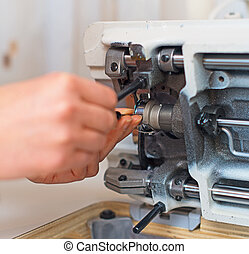Female hand fixing sewing machine. Maintenance.