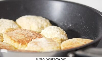 Female hand fries pancakes from cottage cheese in frying pan