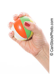 female hand grabs colorful juggling balls on a white background