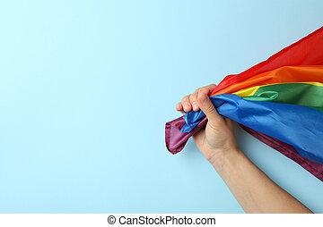Female hand hold LGBT flag on blue background