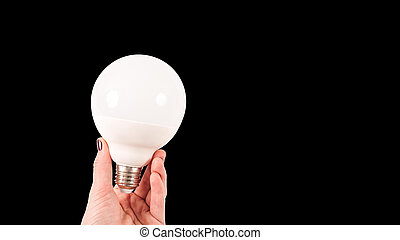 Female hand holding a big white matte light bulb on black background