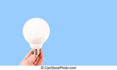 Female hand holding a big white matte light bulb on blue background