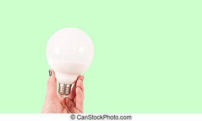 Female hand holding a big white matte light bulb on green background