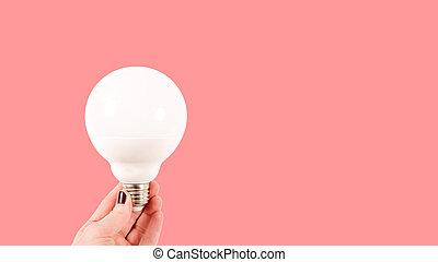 Female hand holding a big white matte light bulb on terracotta background