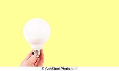 Female hand holding a big white matte light bulb on yellow background