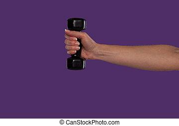 Female hand holding a black dumbbell