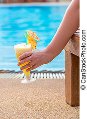 female hand holding a cocktail, picture on the background of the pool