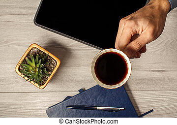 Female hand holding a cup of coffee with notebook on the background