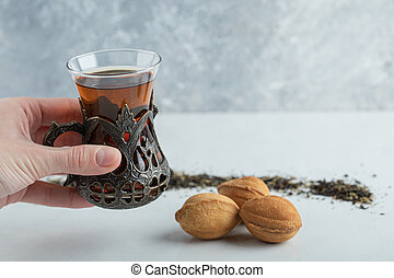 Female hand holding a cup of herbal tea with sweet walnut shaped cookie