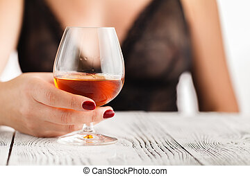 Female hand holding a glass of cognac