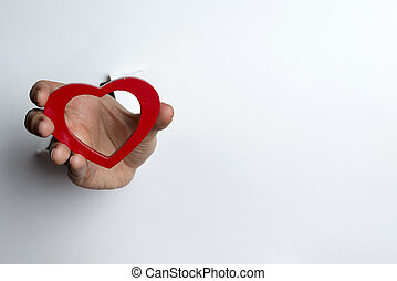 Female hand holding a heart on a white background.