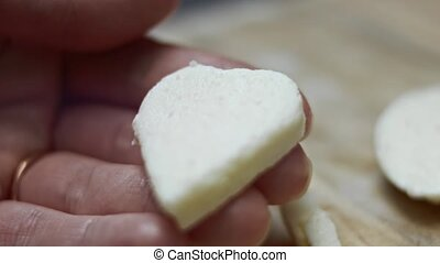 Female hand holding a heart shape of mozzarella cheese on a wooden cutting board background. Preparing food for Valentine's Day. 4k video