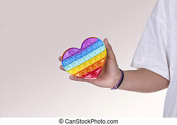 Female hand holding a rainbow heart. LGBT pride rainbow heart and female hand on gray background with copy space