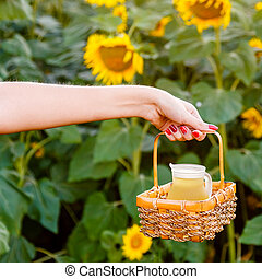 Female hand holding a wicker basket with a jug of sunflower oil