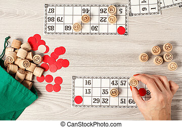 Female hand holding a wooden barrel for a game in lotto