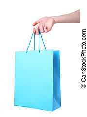 Female hand holding blue shopping bag, isolated on white