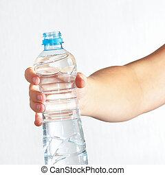 Female hand holding bottle of fresh water