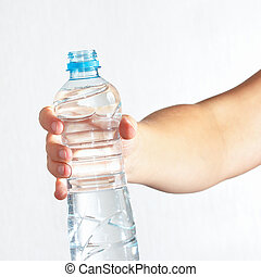 Female hand holding bottle of fresh water