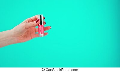 Female hand holding bottle of nail polish against blue background. High quality 4k footage