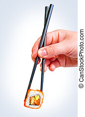 female hand holding chopsticks Japanese roll