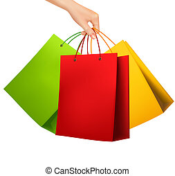 Female hand holding colorful shopping bags. Vector illustration.