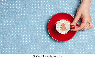 Female hand holding cup of coffee.