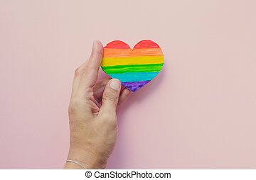 Female hand holding decorative Heart with rainbow stripes on pink background. Human rights concept. Copy space.