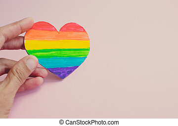 Female hand holding decorative Heart with rainbow stripes on pink background. LGBT pride flag, symbol of lesbian, gay, bisexual, transgender. Homosexual love, Human rights concept. Copy space.