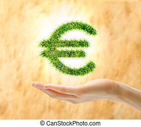 Female hand holding euro sign made of grass