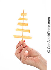 Female hand holding French fries on a stick in white background