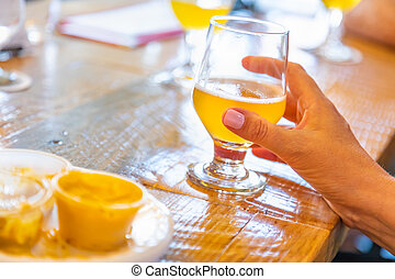 Female Hand Holding Glass of Micro Brew Beer At Bar.