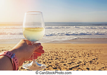 Female hand holding glass of white wine with sea on background.