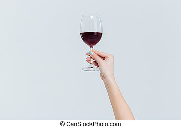 Female hand holding glass with wine