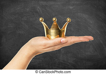 Female hand holding golden crown in front of a chalkboard background