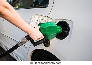 Female hand holding green pump filling gasoline