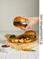 Female hand holding hamburger over diner set with french fries