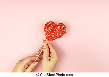 Female hand holding Heart shape lollipop on pink background. Romance flat lay with copy space