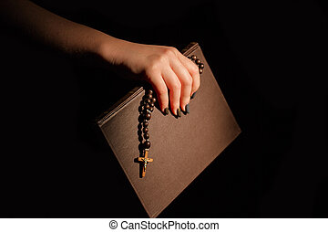 Female Hand holding Holy Bible with crucifix.