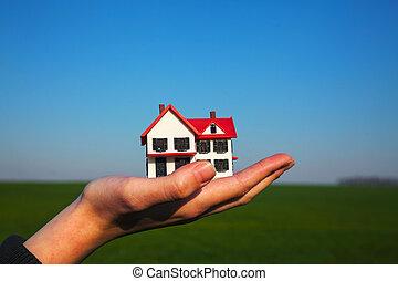Female hand holding model of residential building