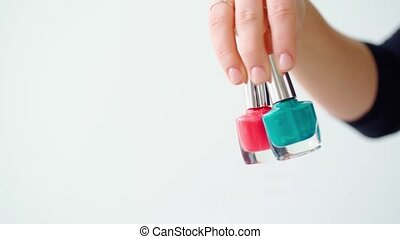 Female hand holding nail polish bottle against white background. High quality 4k footage