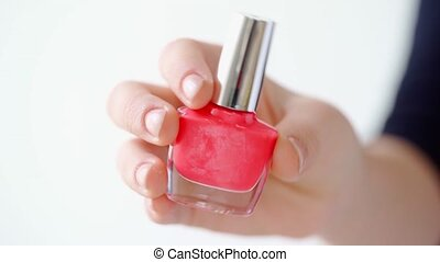 Female hand holding nail polish bottle against white background. High quality 4k footage